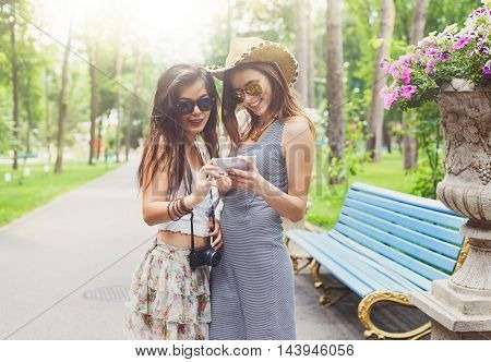 Two girls friends outdoors watching photos at digital camera. Young female tourists in boho chic fashion clothes, laughing and having fun in summer park. Travelling together, lifestyle portrait.