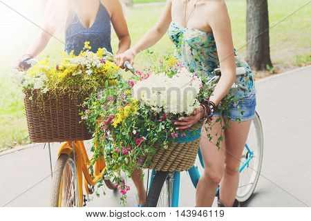 Happy boho chic stylish girls torso with bikes. Beautiful unrecognizable women on bicycles with baskets full of wild flowers. Female friends, youth and happiness, active summer leisure concept.