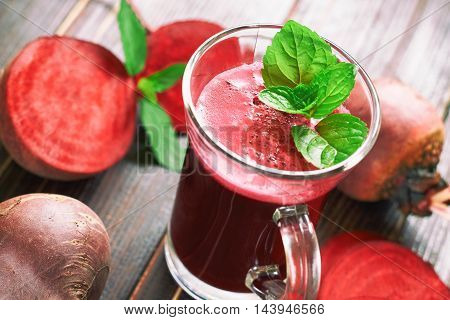 Beetroot juice with mint leaves and beetroots scattered around on wooden background