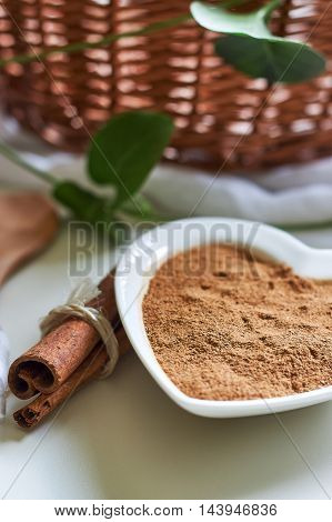 Powdered cinnamon in heart shaped bowl with cinnamon sticks next to it on white surface