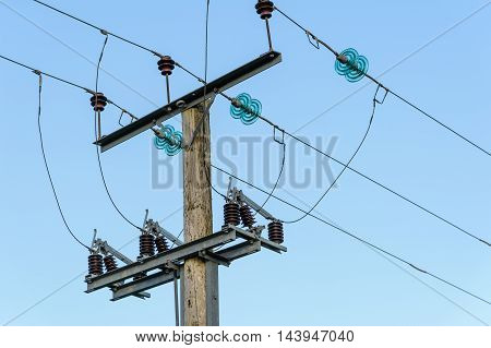 Mains electricity pole with distribution cables and isolators.