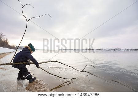 Little boy in winter clothes playing with tree stick and ice on the beach. Nature park and outdoors. Playing child at the river shore. Young explorer by the water. spring in the city. Ice in the water.