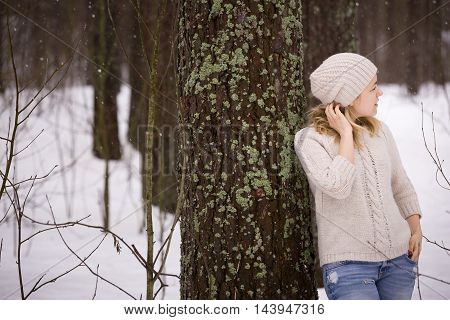 Young blond woman in a warm sweater and a hat standing near a big tree in the forest. Winter walks outdoors. Snow in the forest.