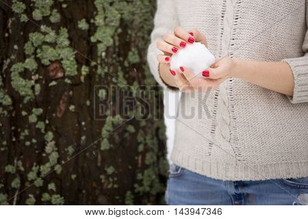 Snowball in hands of a young woman with red manicure and warm sweater. Winter walks outdoors. Snow in the forest.