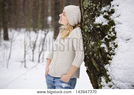Young blond woman in a warm sweater and a hat standing near a tree in the forest. Winter walks outdoors. Snow in the forest.