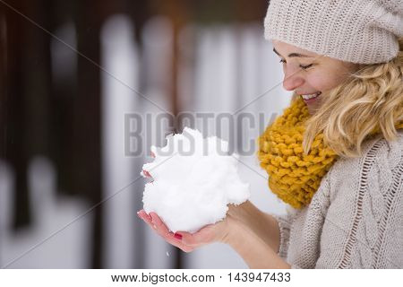 Snow in hands of a young blond woman in warm sweater and yellow scarf. Winter walks outdoors. Snow in the forest. Playing with snowballs