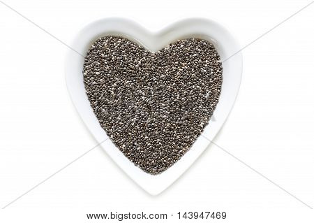 Chia seeds in heart shaped ceramic bowl isolated on white background. Top view