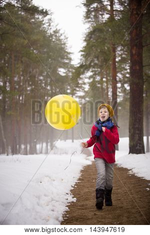 A small happy boy in jeans and a red sweater running in the winter forest and holding a big yellow balloon. Birthday boy with balloon. Birthday celebration. Running boy with balloons.