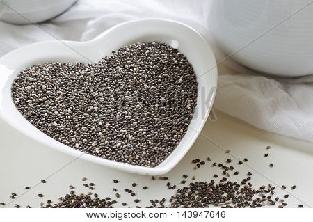 Chia seeds in heart shaped ceramic bowl on white background