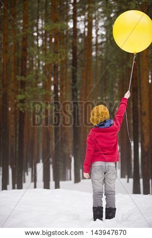 A small happy boy in jeans and a red sweater standing in the winter forest and holding a big yellow balloon. Birthday boy with balloon. Birthday celebration. Standing boy with balloons.