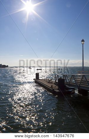 Lamppost In A Pier With The Sun In Front Of Us