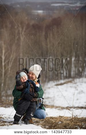 Beautiful woman with her small adorable toddler boy sitting on the ground in a winter day. Forest background. Family walking in the city park. Happy kid and his mom.