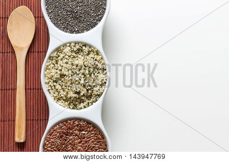 Chia flax and hemp seeds in bowl on white background. Vegan sources of Omega-3. Top view with plenty of copy space