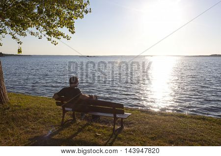 skater watching a sunset sitted in a bench near a lake