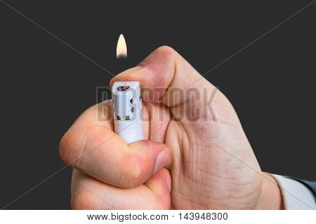 Man Holds White Lighter In Hand And Pressing It With Thumb.