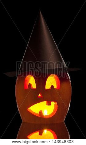 Terrible halloween pumpkin with candle over black background