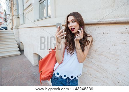 Young surprised brunette woman holding lipstick and looking at her phone outdoors