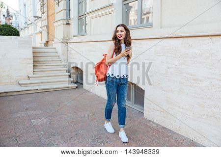 Happy cheerful young girl holding smart phone standing outdoors