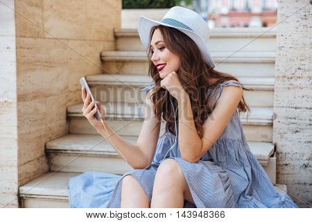Young happy smiling brunette girl sitting and listening to music with earphones outdoors