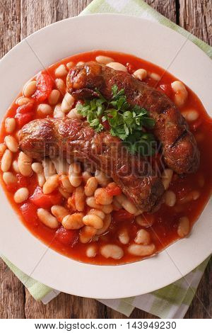 Pork Sausages With Beans And Cooked Tomatoes On A Plate Closeup. Vertical Top View