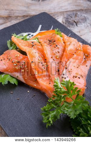 Sliced smoked salmon served on a black board plate