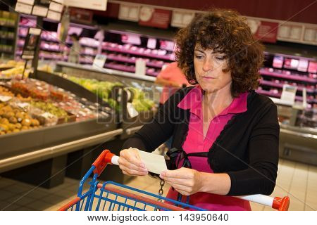 a Brunette woman holding receipt in supermarket