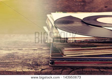 stack of old records on the old wooden background in vintage style