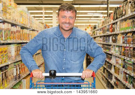 Confident Man Driving Shopping Cart While Grocery Shopping In Supermarket