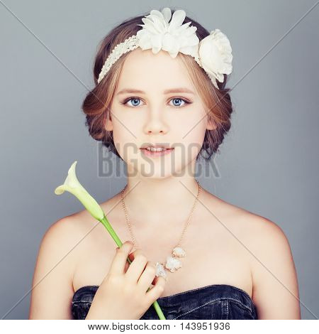 Young Girl holding Lily Flower. Cute Face and Bohemian Boho Chic Hairstyle