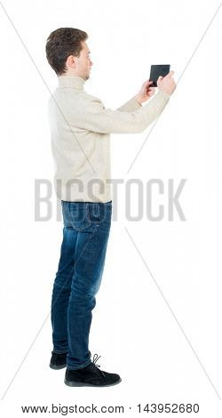 back view of standing business man photographing a phone or tablet. Rear view people collection.  backside view of person.  Isolated over white background. Curly short-haired man in a woolen white