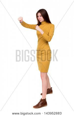 skinny woman funny fights waving his arms and legs. Isolated over white background. Long-haired brunette in a mustard-colored dress in boxing.