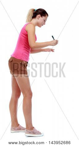 back view of writing beautiful woman. Rear view people collection.  backside view of person. Isolated over white background. Sport blond in brown shorts writes marker.