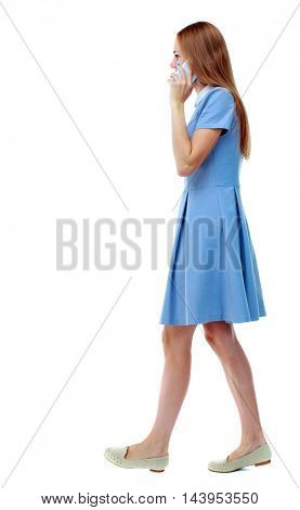 side view of a woman walking with a mobile phone. beautiful girl in motion.  backside view of person.  Rear view people collection. Isolated over white background. Skinny girl in blue dress talking