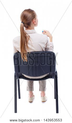 back view of young beautiful  woman sitting on chair.  girl  watching. Rear view people collection.  backside view of person.  Isolated over white background. Skinny girl sitting on an office chair in