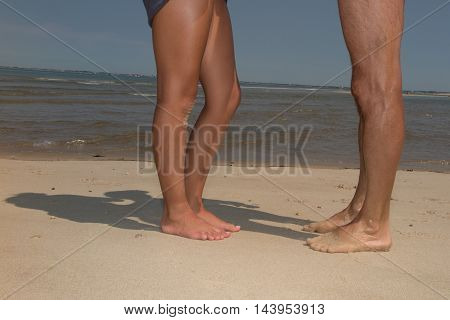 Legs Of Young Kissing Couple On Beach