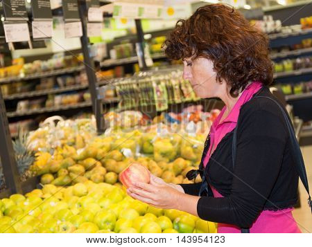 Thoughtful Woman Choosing Apple During Shopping At Fruit Vegetable Supermarket