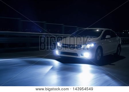 Saratov, Russia - October 23, 2012: White car Honda Civic with xenon headlights fast drive on road at nigh