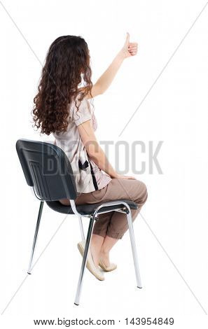 back view of young beautiful  woman sitting on chair and thumbs up. girl  watching. Rear view people collection.  backside view of person.  Isolated over white background. Long-haired curly girl