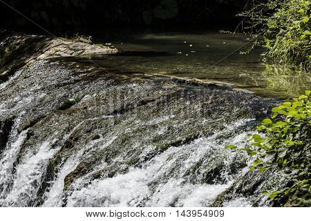 small waterfall and small lake in a forest closeup