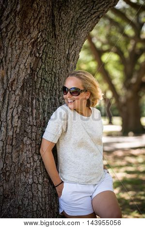 Young blond woman in sunglasses leaning on the old tree in the sunny park and smiling. Relax in the summer park outdoors. Healthy lifestyle. Vacations.