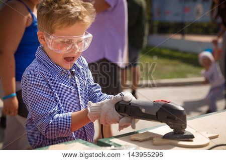 Cute little kid boy in plastic safe glasses grinding wooden board outdoors. Child working on wood with instrument. Learning to work with instruments. Future handyman