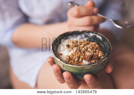 Young woman with muesli bowl. Girl eating breakfast cereals with nuts pumpkin seeds oats and yogurt in bowl. Girl holding homemade granola. Healthy snack or breakfst in the morning.