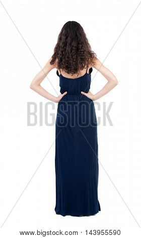 back view of standing young beautiful  woman.  girl  watching. Rear view people collection.  backside view of person. The dark curly girl in blue evening dress standing with hands on hips.