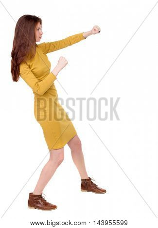 skinny woman funny fights waving his arms and legs. Isolated over white background. Long-haired brunette in a mustard-colored dress hands fights.
