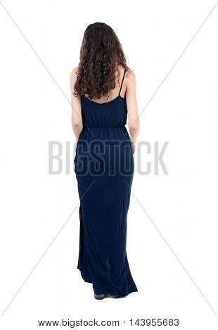 back view of standing young beautiful  woman.  girl  watching. Rear view people collection.  backside view of person. The dark curly girl in a blue evening dress is holding the dress.