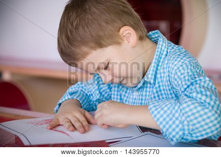 Cute little preschool kid boy in a blue plaid shirt drawing on the paper and smiling. Creative child at the table. Preschool art activities. Leisure with children. Young artist.