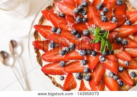Homemade cheesecake decorated with organic strawberries blueberries fresh mint and cream. Nice pie for a holiday celebration or birthday party. Beautiful cake on a glass plate with silver spoons.