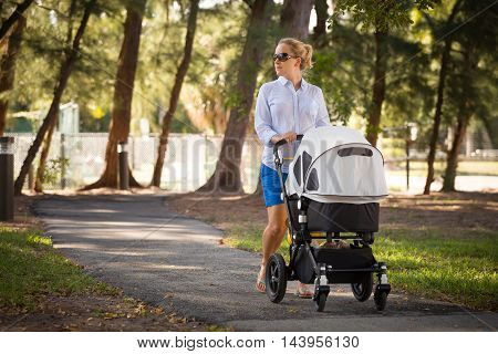 Young mother walking and pushing a stroller in the park. Mother strolling with newborn. Beautiful happy mother with pram outdoors. Summer walks in the sunny day. Girl with carriage.
