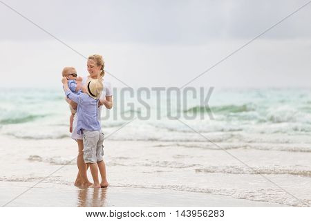 Young mother in white dress walking with her two little boys along the ocean beach. Woman with baby and boy enjoying vacation by the sea. On the empty beach. Motherhood. Water background. copy space.