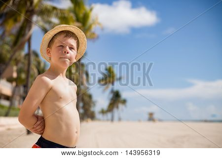 Portrait of adorable kid boy in a straw hat standing on the sandy beach looking into distance and smiling. Outdoors. Summer time. Happy child by the sea. School boy on vacations on the ocean beach.